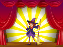 A witch at the stage with a red curtain Royalty Free Stock Images