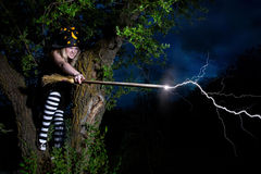 Witch strikes lightning from the broomstick. Sitting on the tree Stock Photo
