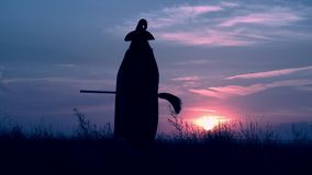 A witch stroll halloween on the hill evening skyline. Sorceress in cloak and hat holding broom walking on field on the background a blue sky with clouds all stock video