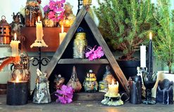 Witch table with black candles, magic bottles, herbs. Wicca, esoteric, divination and occult concept with vintage magic objects for mystic rituals, Halloween royalty free stock photos