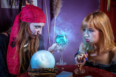Witch tempting a girl to drink a potion. Evil soothsayer trying to trick young blonde women into drinking a bubbly blue potion Royalty Free Stock Images