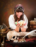Witch with trick or treat candy. Young halloween witch holding a handful of trick or treat candy (the book is 300 years old, no copyright problems Stock Photography