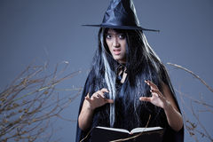 Witch using spell book. Young witch casting a spell and holding a book Royalty Free Stock Images