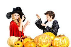Witch and vampire. Boy and girl teenagers wearing halloween costumes posing with pumpkins. Isolated over white. Autumn holidays Royalty Free Stock Photos
