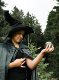 Witch with wand and glass ball. In hand Stock Photo