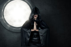 Witch wearing black hood. Image of witch wearing black hood casting spell Stock Image