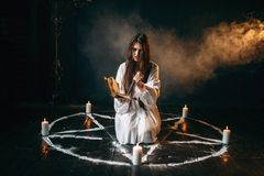 Witch in white shirt holds knife and reads spell. Pentagram circle with candles, dark magic ritual process. Occultism and exorcism Royalty Free Stock Photos