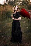 Witch with wings and snake. Stands in the swamp. Halloween concept Stock Photography