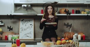 A witch wit black lips eating soo funny the snack on Halloween party, she is sitting on kitchen table and holding the