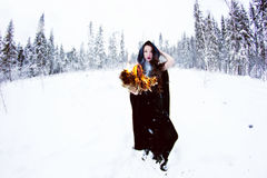 Witch or woman in black cloak with fire ball in white snow forest Stock Photos