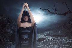Witch woman with black costume wearing cloak and holding knife Stock Photo