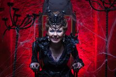 The witch woman growls. Woman in a black witch costume sits on a throne in a red room. She growls Royalty Free Stock Image