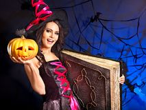 Witch woman holding old book and pumkin. Happy witch woman holding old book and pumkin Royalty Free Stock Image