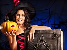 Witch woman holding old book and pumpkin. Happy witch woman holding old book and pumpkin Stock Photography