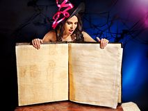 Witch woman holding open book. Royalty Free Stock Images