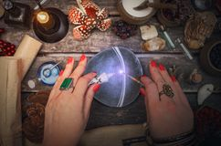 Witchcraft. Witch woman is preparing a magic potion on paranormal table background. Witchcraft concept royalty free stock photos