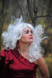 Witch in the woods on Halloween. Beautiful young woman in the image of the witch in the woods on Halloween stock photo