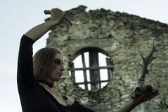 Sinister female ritual. Witch - young woman in black dress with ominous make-up conducts an sinister pagan rite among ancient ruins stock photos