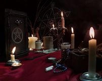 Witchcraft composition with candles, book and pentagram royalty free stock image