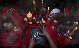 Witchcraft composition with candles, skull and pentagram. Witchcraft composition with burning candles, human skull, magic books, jewelry, tarot cards and Stock Photo