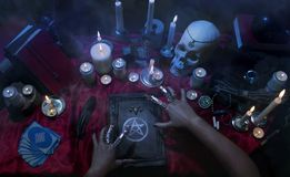 Witchcraft composition with candles, skull and pentagram. Witchcraft composition with burning candles, human skull, magic books, jewelry, tarot cards and Royalty Free Stock Image