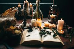 Witchcraft, dark magic, candles with ritual book. On the table, nobody. Occult and esoteric symbols Royalty Free Stock Images
