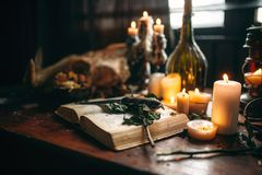 Witchcraft, dark magic, candles with ritual book. On the table, nobody. Occult and esoteric symbols Stock Photography