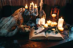 Witchcraft, dark magic, candles with ritual book. On the table, nobody. Occult and esoteric symbols Stock Photo