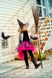 Witchcraft girl. Pretty little girl in a costume of witch with her magic broom celebrating halloween. Trick or treat. Halloween party Royalty Free Stock Image