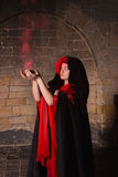 Witchcraft in gothic style. Gothic witch holding red smoke in a medieval castle Royalty Free Stock Photos