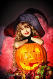 Witchcraft kid. Little girl in a costume of witch posing with pumpkins over dark background Royalty Free Stock Photo