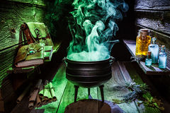 Witcher cauldron with blue and green smoke for Halloween. On wooden table Stock Photo