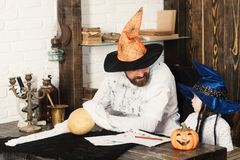 Witcher and little magician make decor for Halloween. Man and kid in witch hats look at each other and play with pumpkins. Halloween and party concept. Guy and Stock Image