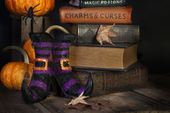 Witches Boots and Books. Purple and black striped stylish witches boots, charms and magic potions books, pumpkins and spiders on dark background Stock Photography