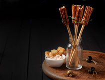 Witches broomsticks at a Halloween party. Made from bread sticks and pretzels standing in a glass jar on a table decorated with creepy spiders made from olives Stock Images