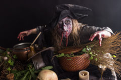 Witches kitchen. Witches bends over a table with witches ingredients Stock Photo