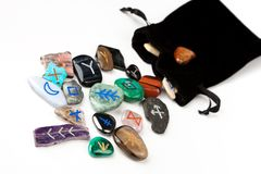 Witches runes. Divination stones called Witches runes, scattering out of black velvet bag, isolated on white Royalty Free Stock Image