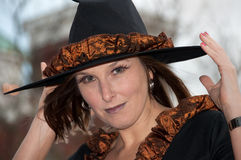 Witchy Witch. A witch casts a spellbinding gaze as she adjusts the brim of her hat Stock Photo