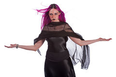 Witchy woman. Isolated on a white background a beautiful young woman in a long black dress and purple hair and a blach shawl holds her arms out as she stares Royalty Free Stock Photos