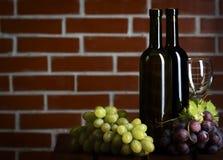 Wite и бутылки красного вина на предпосылке кирпичной стены Стоковые Фото