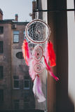 Wite handmade dreamcatcher against the old house. Background hanging on the window Stock Images