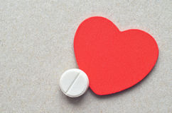 Wite pill and red heart Royalty Free Stock Image