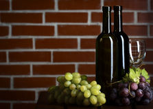 Wite and red wine bottles on brick wall background Stock Photos