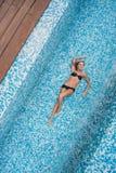WithBeautiful schlankes Mädchen des schönen schlanken Mädchens mit dem blonden Haar in einem Badeanzug, der im Pool, Draufsicht l Lizenzfreies Stockfoto