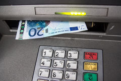 Withdraw money from ATM machine. Withdrawing euros from ATM machine Stock Photography