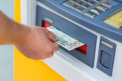 Withdraw money from ATM. Taking money out of the ATM Stock Image