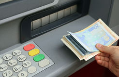 Withdrawal of money in European banknotes from automatic cash ma Stock Photos