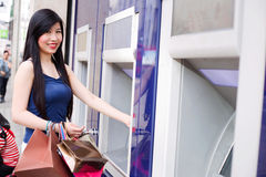 Withdrawing cash. Young japanese woman withdrawing cash from an atm while out shopping Stock Image