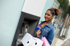Withdrawing cash. Young woman withdrawing cash at the atm Royalty Free Stock Photography