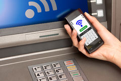Withdrawing money atm with mobile phone (NFC near field communic. Withdrawing money from atm with a mobile phone a NFC terminal Stock Image